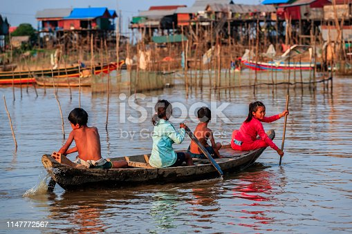 Group of happy Cambodian children rowing a boat on Tonle Sap, Cambodia