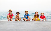 group of happy children by the sea in summer