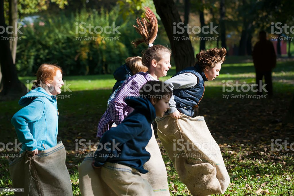 Group of happy children enjoying in a sack race stock photo