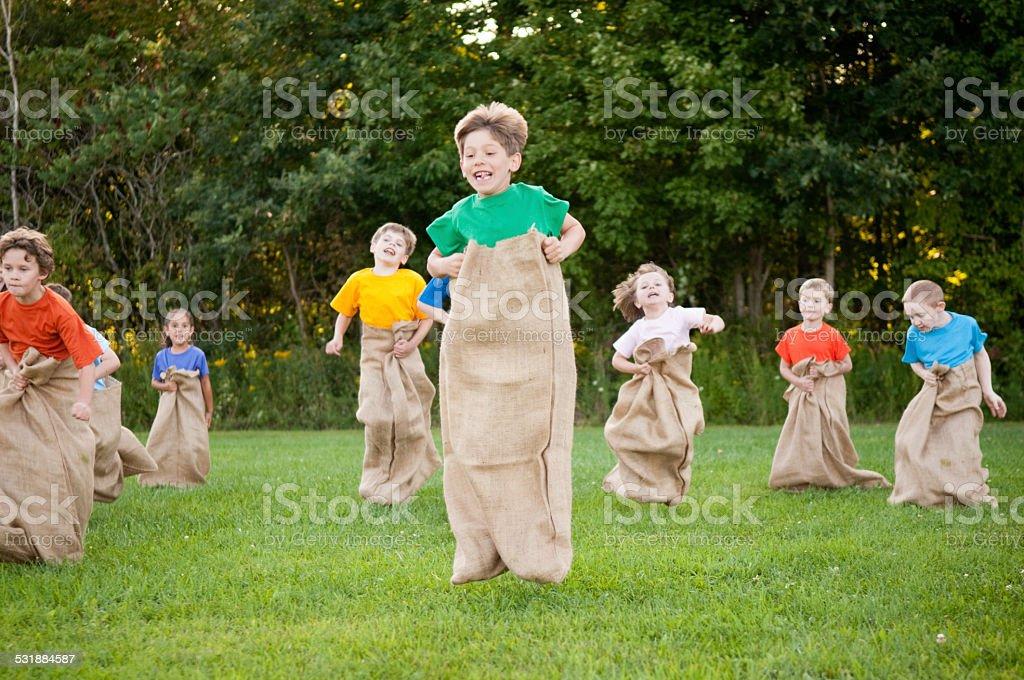 Group of Happy Children Having Potato Sack Race Outside stock photo