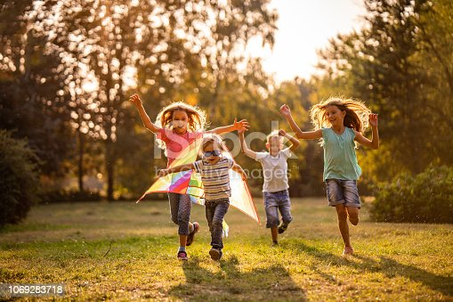 istock Group of happy children running in public park 1069283718