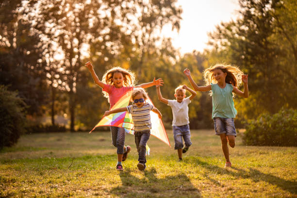 Group of happy children running in public park Happy kids playing in nature with flying dragon children only stock pictures, royalty-free photos & images