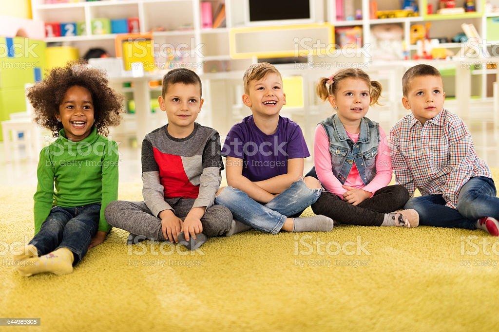 Group of happy children sitting on the floor at kindergarten. stock photo