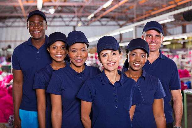 group of happy clothing factory workers stock photo