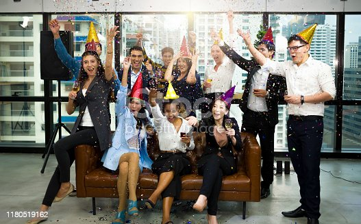 Group of happy colleagues having fun at a new year celebration ahead or business success. Coworkers with diverse ethnicities are toasting wine or champagne glasses at the office party.