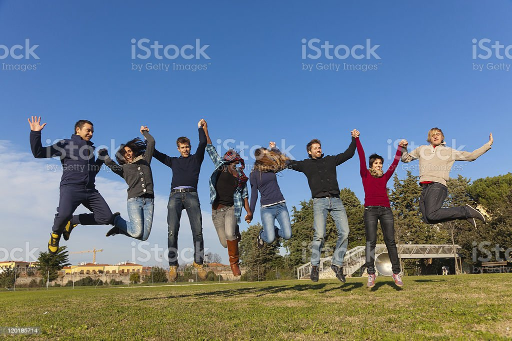 Group of Happy College Students Jumping at Park royalty-free stock photo
