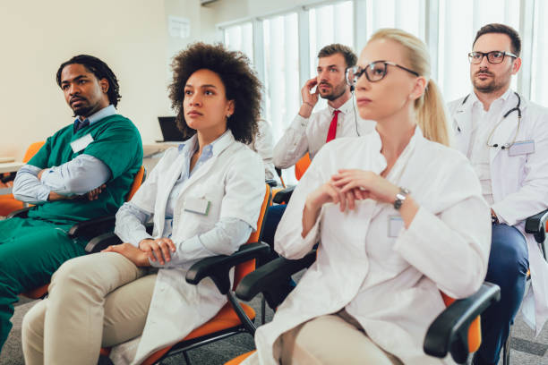 Group of happy doctors on seminar in lecture hall at hospital stock photo