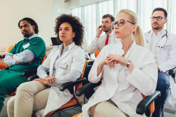 Grupo de médicos felices en seminario en salón de conferencias en el hospital - foto de stock