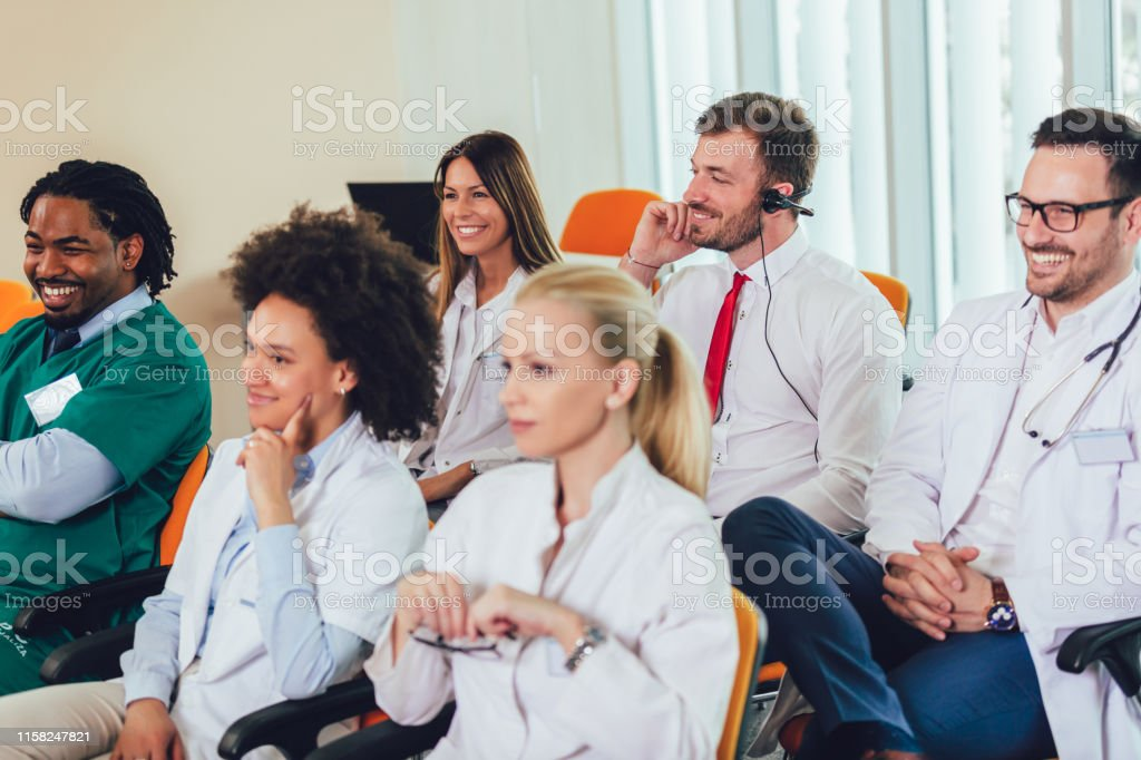 Group of happy doctors on seminar in lecture hall at hospital