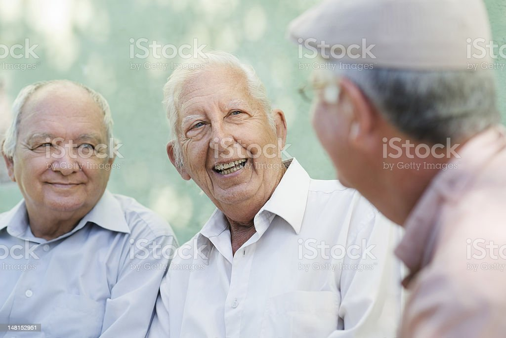 Group of happy elderly men laughing and talking stock photo