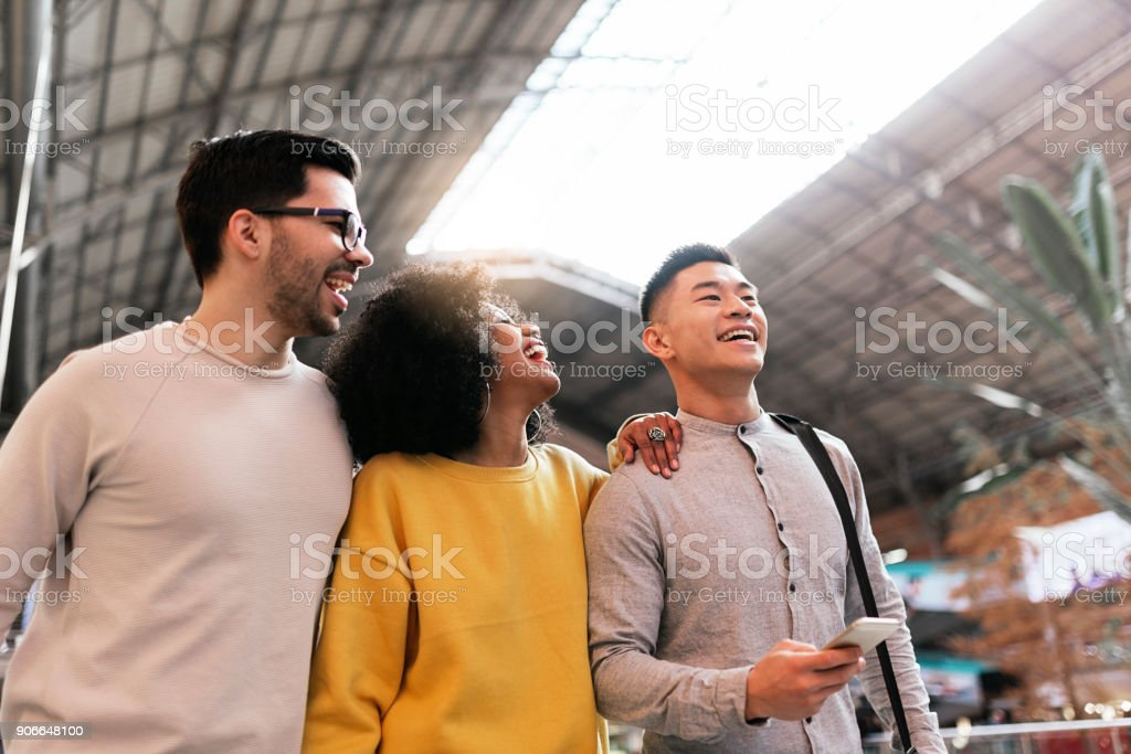 Group of happy friends chatting in the train station. stock photo
