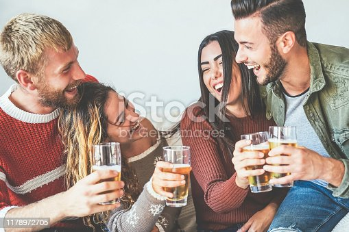 istock Group of happy friends cheering with beer at home - Millennial Young people having fun drinking and laughing together sitting on sofa - Friendship, entertainment and youth lifestyle holidays 1178972705