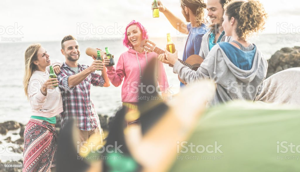 Group of happy friends cheering with beers in camping - Trendy people having fun playing music and laughing together - Focus on left woman - Travel, vacation, party and friendship concept stock photo