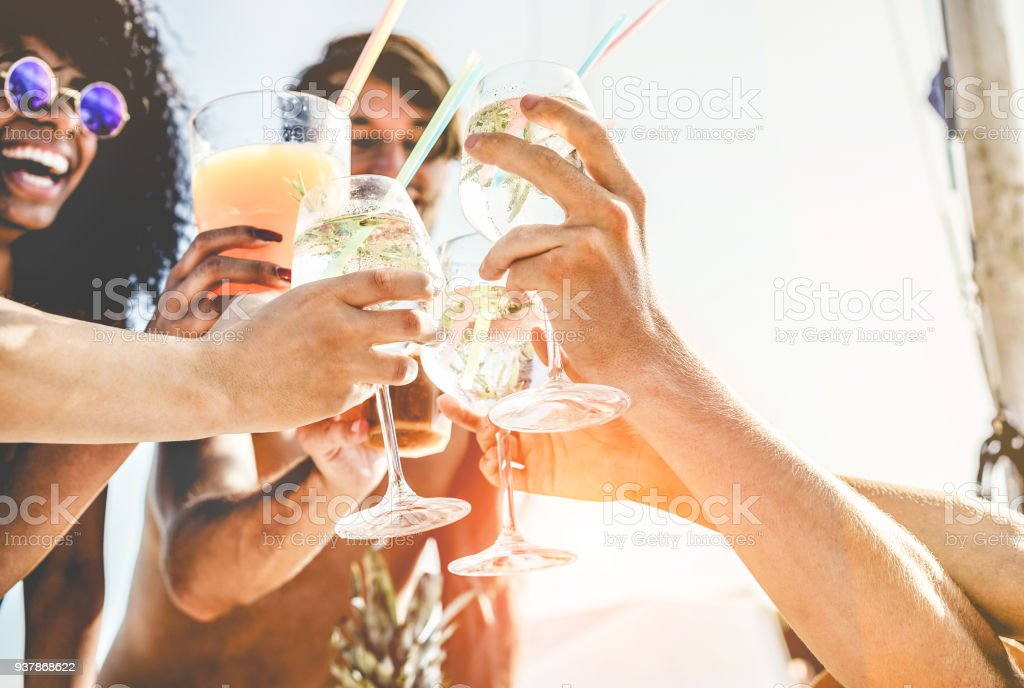 Group of happy friends cheering with tropical cocktails at boat party - Young people having fun in caribbean sea tour - Youth and summer vacation concept - Focus on bottom hands glass stock photo