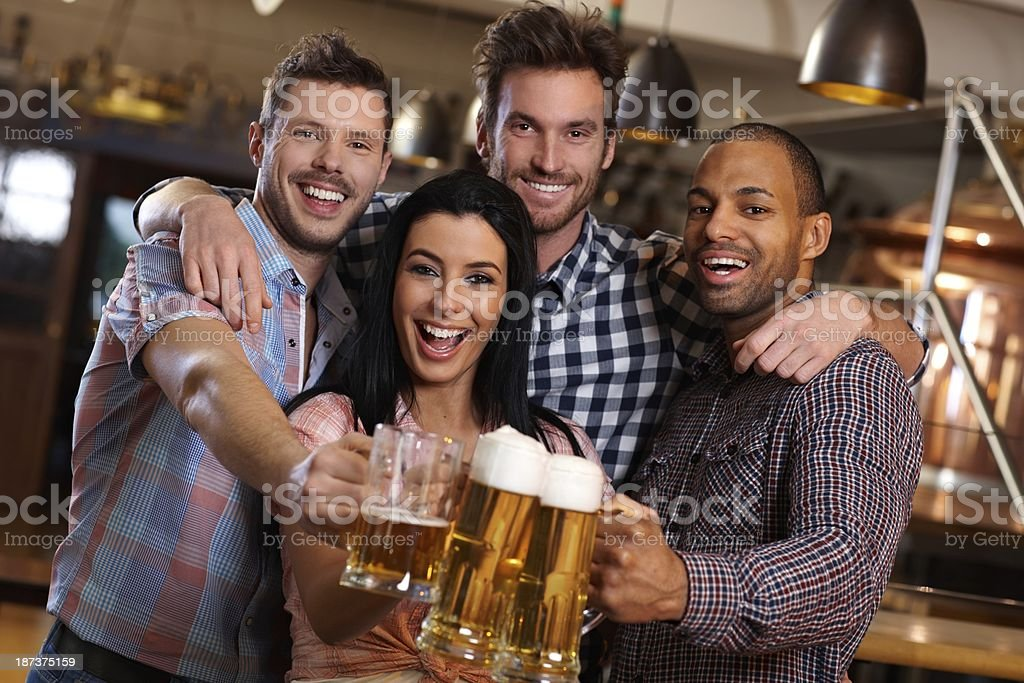Group of happy friends clinking with beer in pub royalty-free stock photo