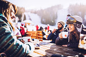 Happy skiers talking on a break in a cafe at mountain.