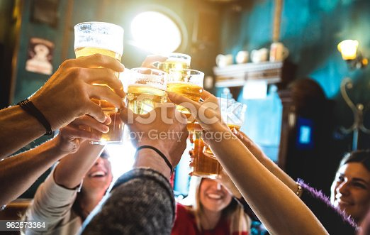 istock Group of happy friends drinking and toasting beer at brewery bar restaurant - Friendship concept with young people having fun together at cool vintage pub - Focus on middle pint glass - High iso image 962573364