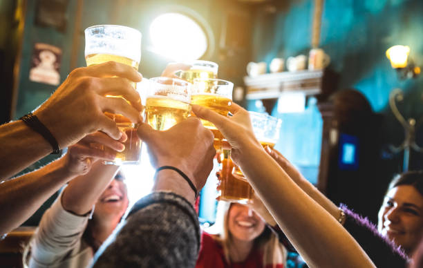 group of happy friends drinking and toasting beer at brewery bar restaurant - friendship concept with young people having fun together at cool vintage pub - focus on middle pint glass - high iso image - happy hour stock photos and pictures