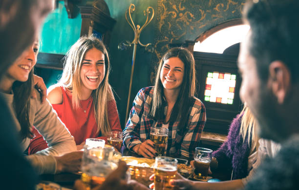 group of happy friends drinking beer at brewery bar restaurant - friendship concept with young millenial people enjoying time together having fun vintage pub - focus right woman - high iso image - after work stock photos and pictures