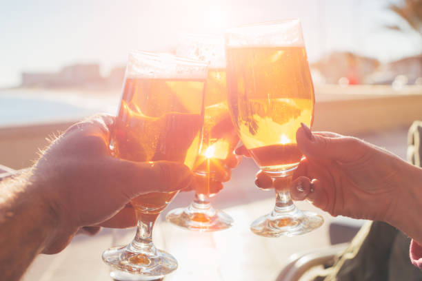 Group of happy friends drinking beer outdoors together - hands with beer glasses clinking on a sunny backgraund - concept of friendship and celebration