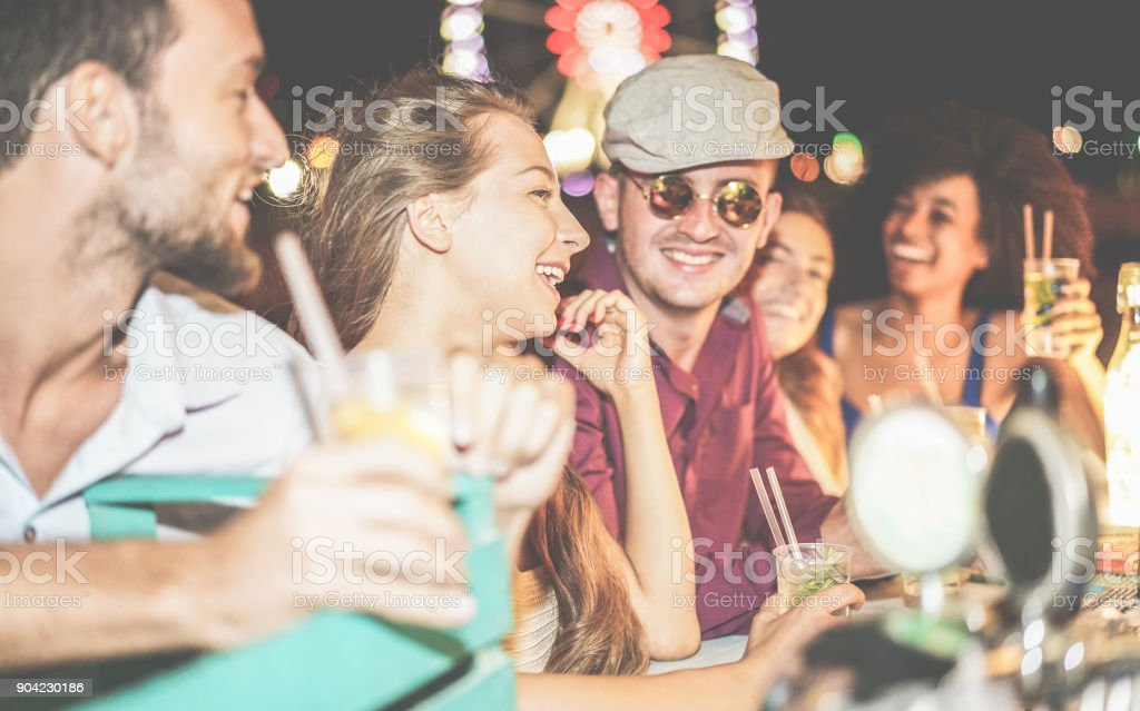 Group of happy friends drinking cocktails and laughing at beach party outdoor - Young tourist having fun in summer vacation - Focus on left girl eye - Nightlife, holidays and youth concept stock photo