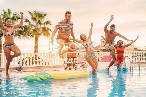 istock Group of happy friends drinking jumping in pool sunset party outdoor - Young diverse culture people having fun in tropical vacation - Holiday, youth and friendship concept - Main focus on left man 885530572