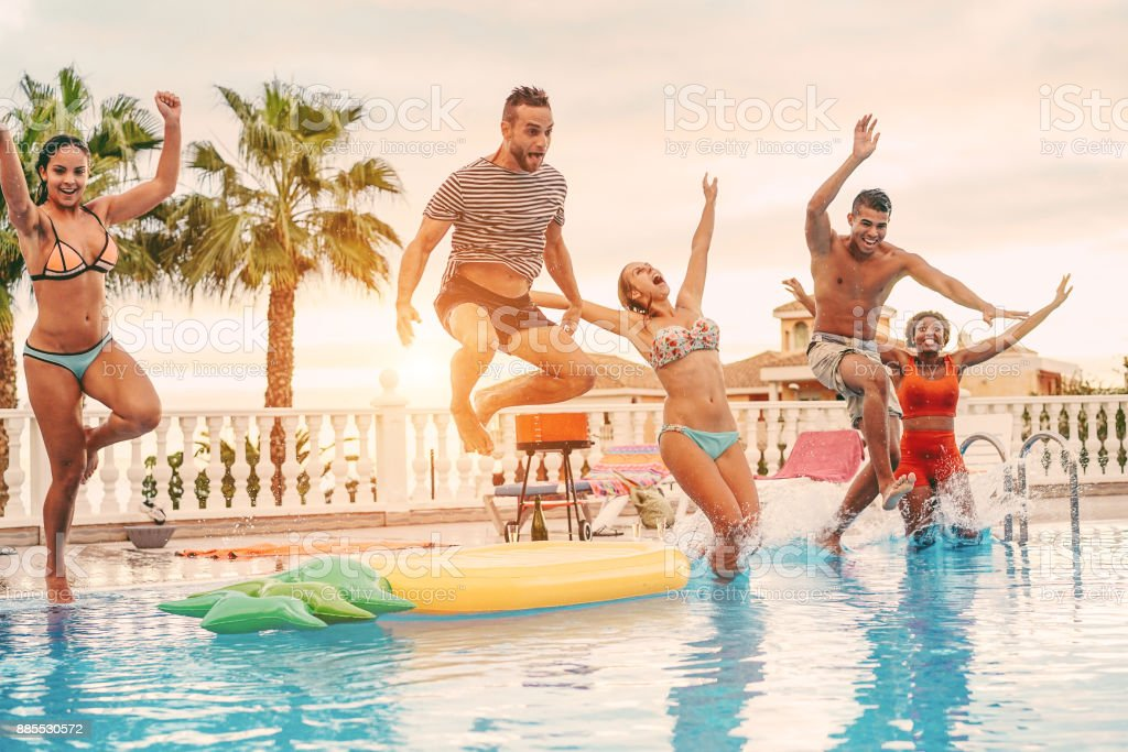Group of happy friends drinking jumping in pool sunset party outdoor - Young diverse culture people having fun in tropical vacation - Holiday, youth and friendship concept - Main focus on left man stock photo