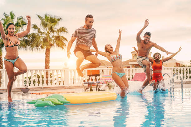 Group of happy friends drinking jumping in pool sunset party outdoor - Young diverse culture people having fun in tropical vacation - Holiday, youth and friendship concept - Main focus on left man - foto stock