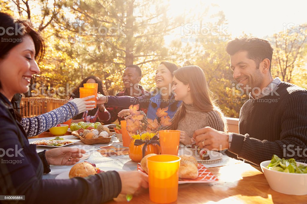 Group of happy friends eat and drink at a table at stock photo