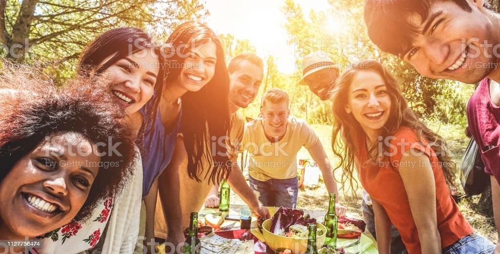 Gruppe der happy Friends, Essen und trinken Bier am Grill-Abendessen bei Sonnenuntergang - Erwachsene Menschen, die gemeinsame Mahlzeit im freien - Fokus auf Links Gesichter - Sommer Lifestyle, Food und Freundschaft Konzept – Foto