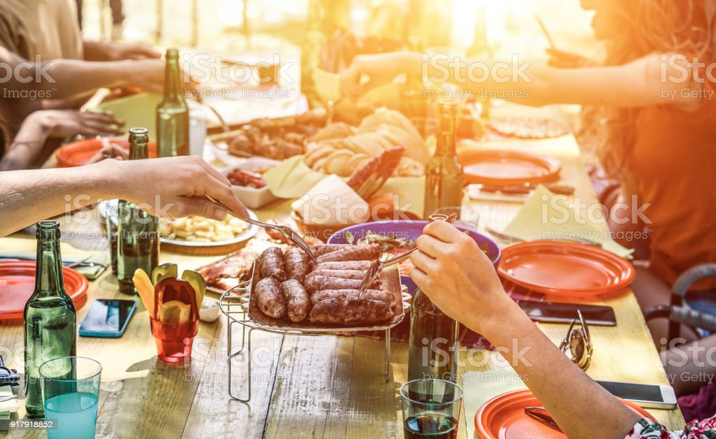 Group of happy friends eating and drinking beers at barbecue dinner at sunset - Adult people having meal together outdoor - Focus on fork sausages - Summer lifestyle, food and friendship concept stock photo