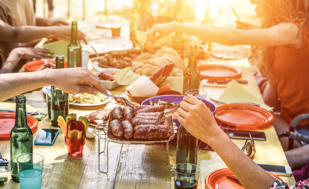 group of happy friends eating and drinking beers at barbecue dinner at sunset - adult people having meal together outdoor - focus on fork sausages - summer lifestyle, food and friendship concept - barbecue grill stock photos and pictures