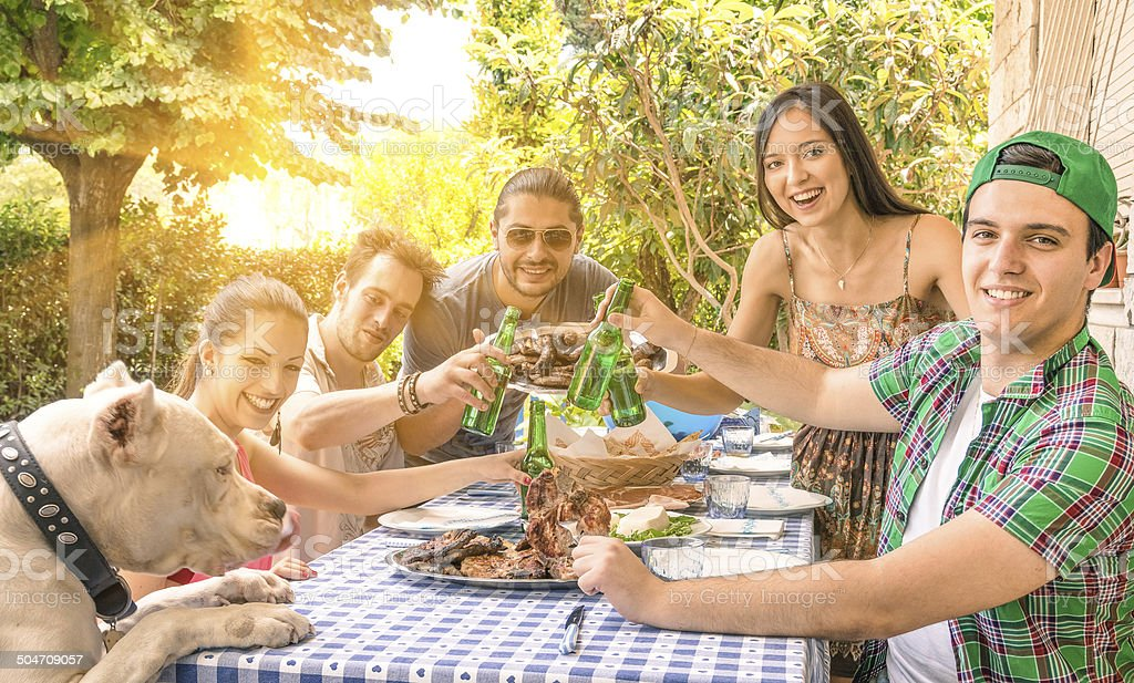 Group of happy friends eating and toasting at garden barbecue stock photo
