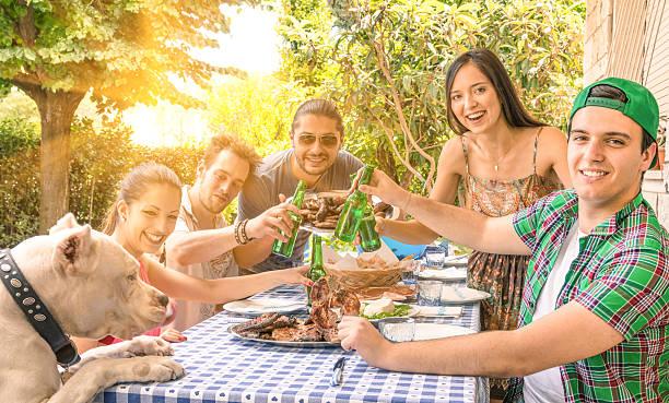 gruppe von glücklichen freunde essen und rösten im garten-barbecue - paletten terrasse stock-fotos und bilder