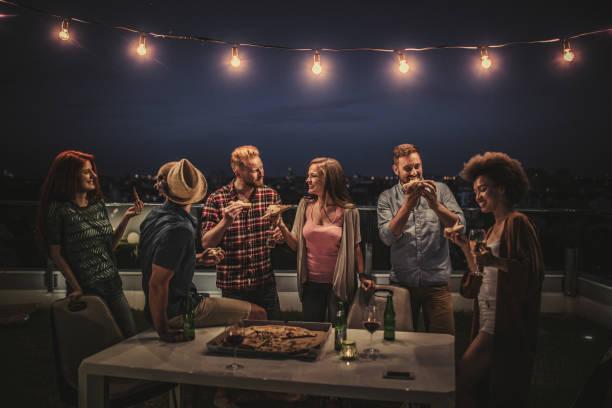 freundeskreis glücklich essen pizza auf einer dinner-party im penthouse balkon. - terrassen lichterketten stock-fotos und bilder