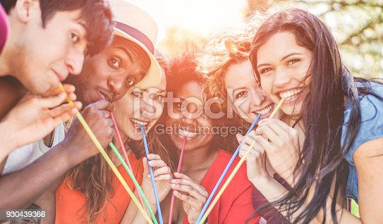istock Group of happy friends enjoying drink outdoor at summer party - Young people having fun together and drinking tropical cocktail - Focus on three center girls - Youth lifestyle and friendship concept 930439366
