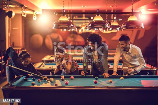 Young happy people playing snooker in a pub and having fun together.