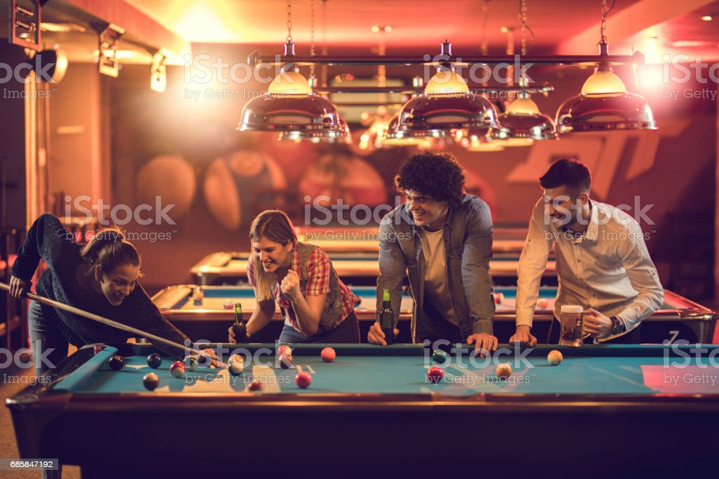 Group of happy friends enjoying in billiard game in a pool hall. stock photo