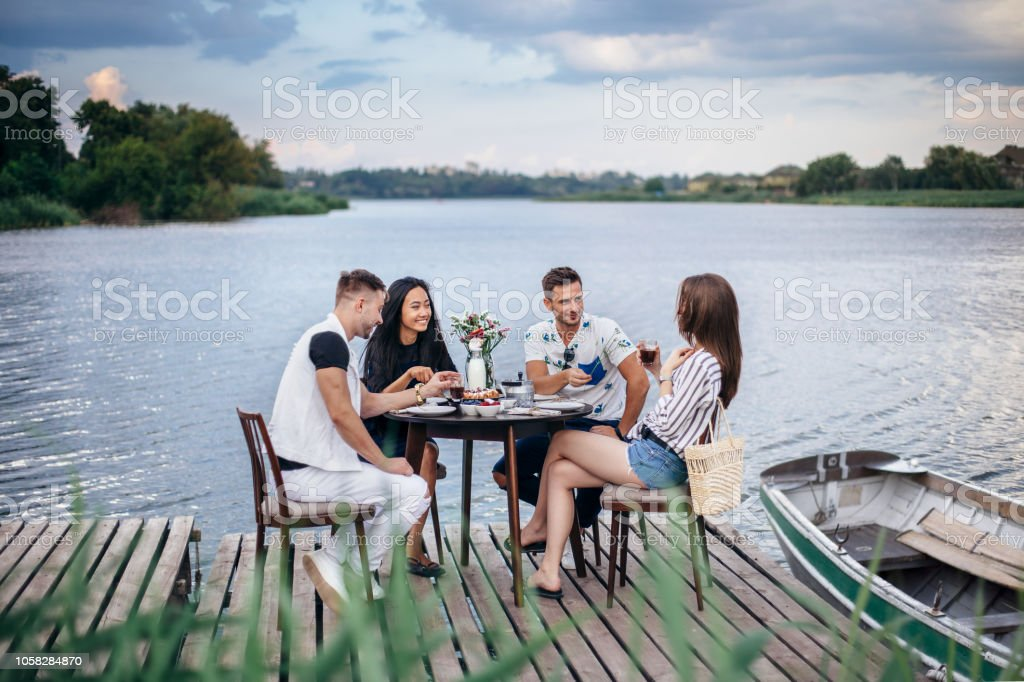 Group of happy friends gathering to having dinner together at summer...