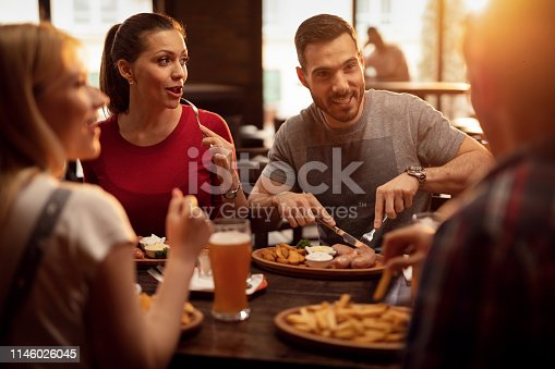Young happy people eating in a pub and talking to each other.