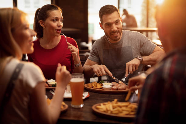 Group of happy friends having a lunch in a tavern. Young happy people eating in a pub and talking to each other. restaurants stock pictures, royalty-free photos & images
