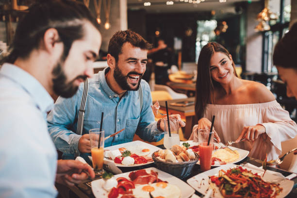 Group of Happy friends having breakfast in the restaurant stock photo