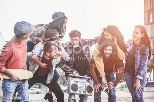 Group of happy friends having fun walking on city streets outdoor - Young millennials hanging out together - Millennial generation, youth and social lifestyle concept - Focus on right guys faces