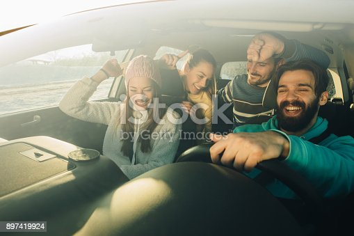 istock Group of happy friends having fun while dancing during a road trip in the car. 897419924