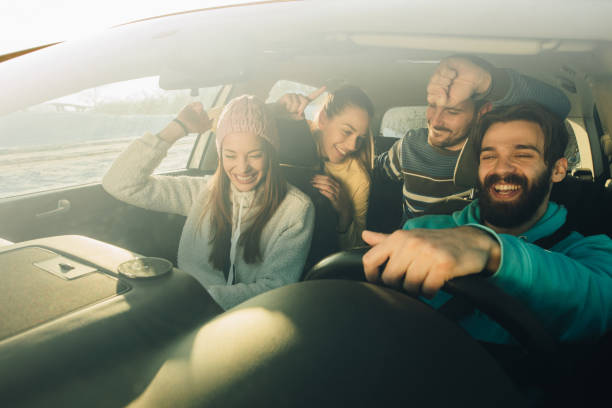group of happy friends having fun while dancing during a road trip in the car. - car interior stock photos and pictures