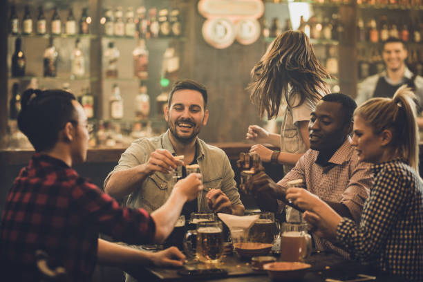Group of happy friends having fun while toasting with vodka shots in a pub. Cheerful friends having fun while toasting with shots during their night out in a bar. vodka stock pictures, royalty-free photos & images