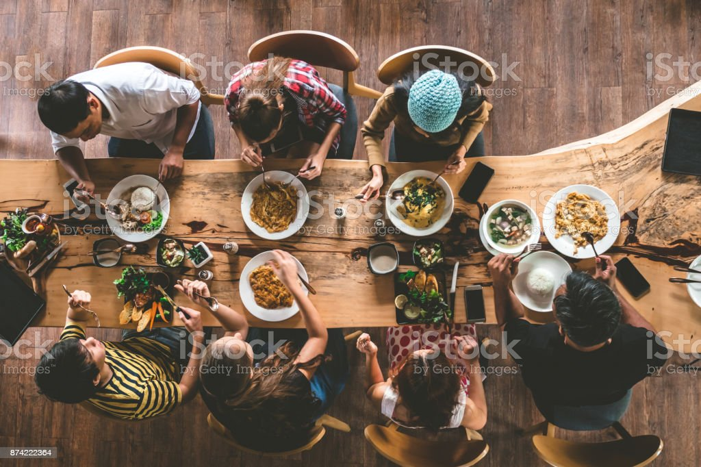 Group of happy friends having nice food and drinks, enjoying the party and communication, Top view of Family gathering together at home for eating dinner. stock photo