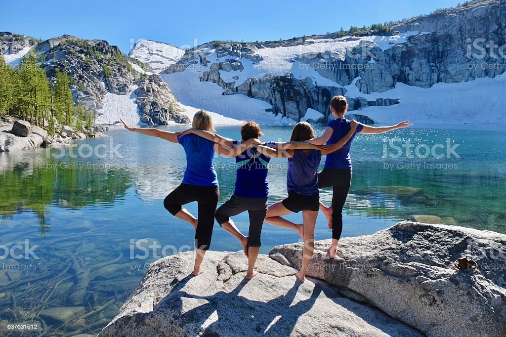 Group of happy friends in yoga pose by beautiful lake. – Foto