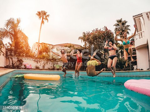 Group of happy friends jumping in pool at sunset time - Crazy young people having fun making party in exclusive tropical house - Holidays, summer, vacation and youth lifestyle concept