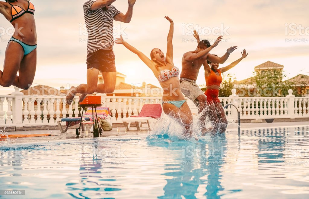 Group of happy friends jumping in pool party at sunset - Young diverse culture people having fun in tropical vacation - Holiday, youth lifestyle and friendship concept - Main focus on blond woman face stock photo
